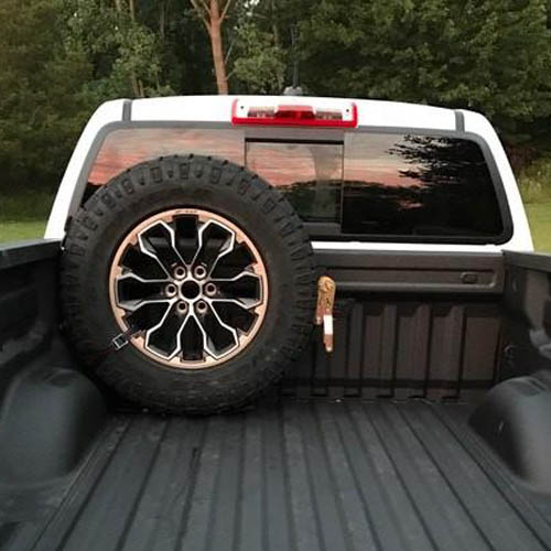 two inch strap holding down tire on pickup truck